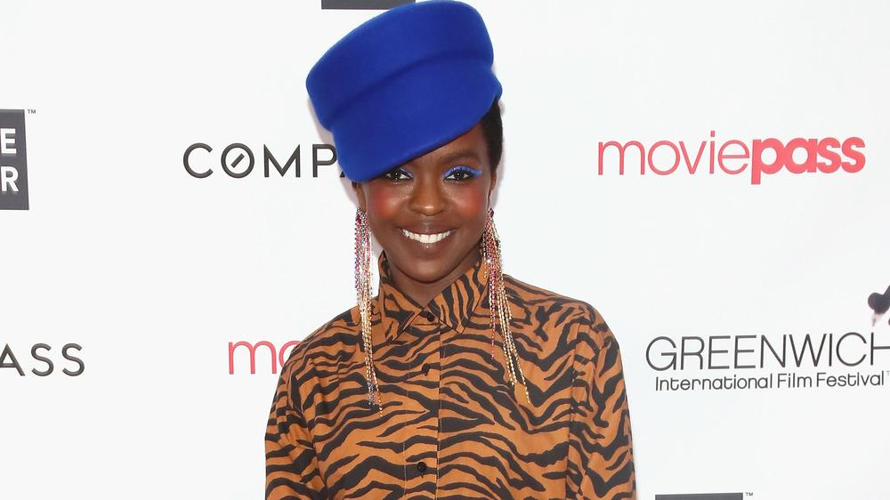 Lauryn Hill sonriendo con sombrero azul y blusa con estampado de tigre