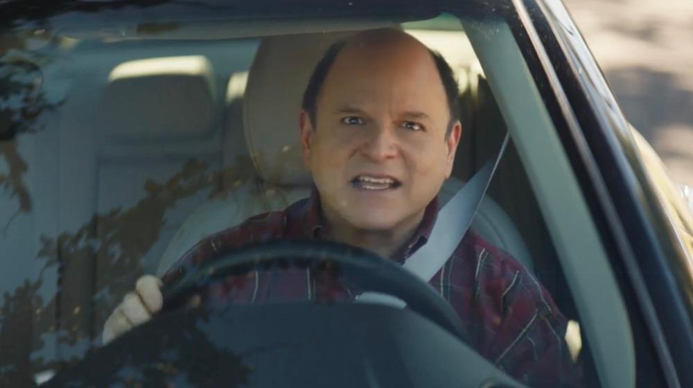 Jason Alexander mirando al frente desde el asiento del conductor de un automóvil