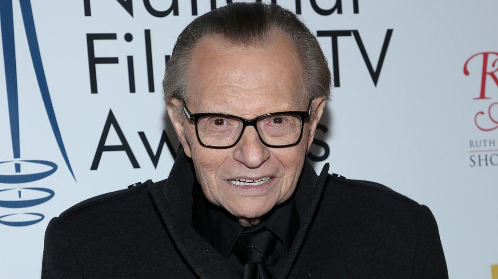 Larry King sonriendo en la alfombra roja