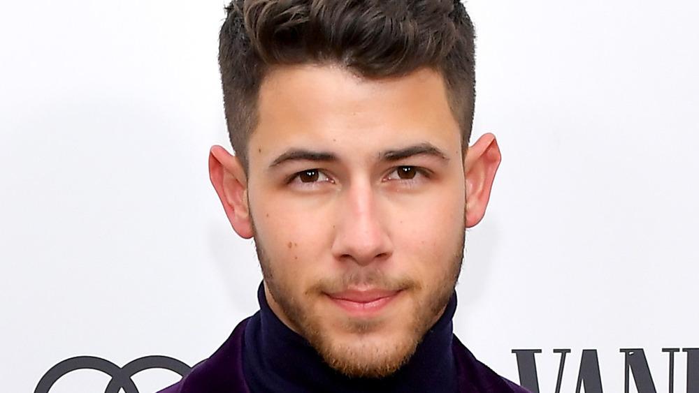 Nick Jonas mira al frente sonriendo levemente posando para las cámaras