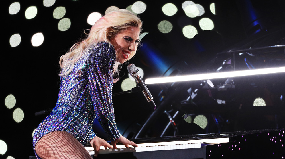 Lady Gaga levanta la pierna sobre su piano y canta en el micrófono en el espectáculo de medio tiempo del Super Bowl 2017