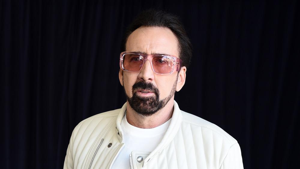 retrato de Nicolas Cage con una chaqueta blanca y gafas de sol rosas