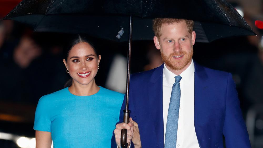 El príncipe Harry y Meghan Markle con paraguas
