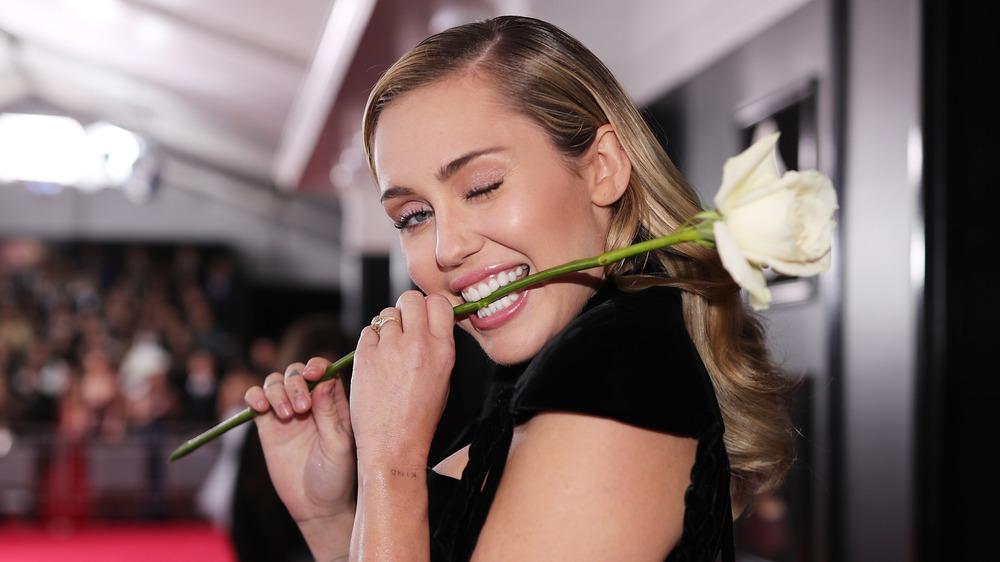 Miley Cyrus guiñando un ojo y mordiendo el tallo de una flor