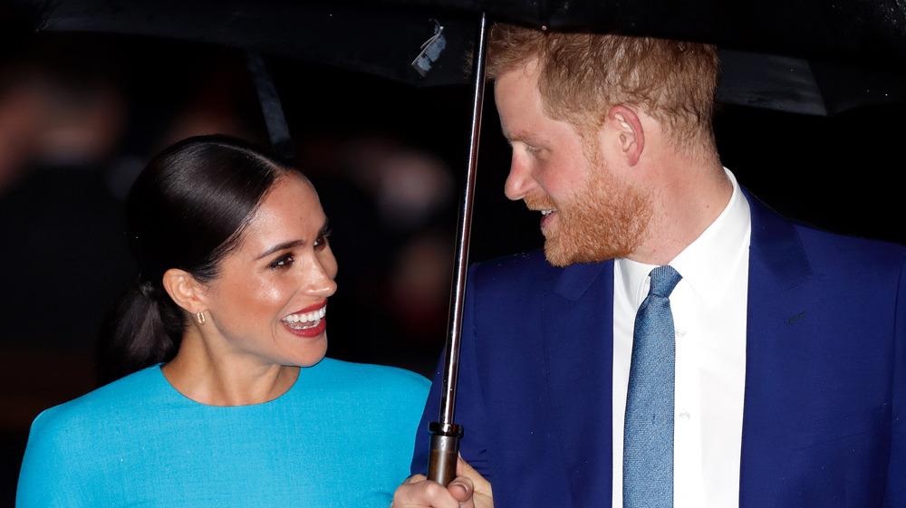 Meghan Markle y el príncipe Harry se sonríen bajo un paraguas