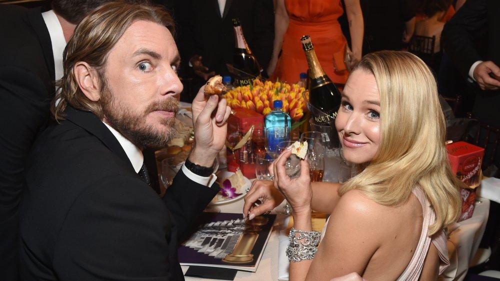 Dax Shepard y Kristen Bell en la mesa con comida del tamaño de un bocado en las manos