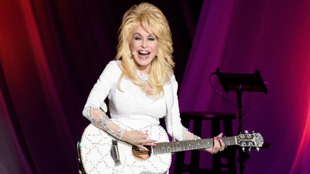 Dolly Parton tocando la guitarra en el escenario