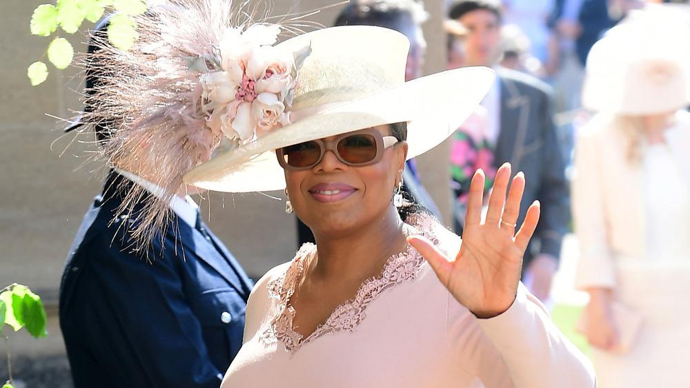 Oprah Winfrey con un gran sombrero de plumas y gafas de sol saludando