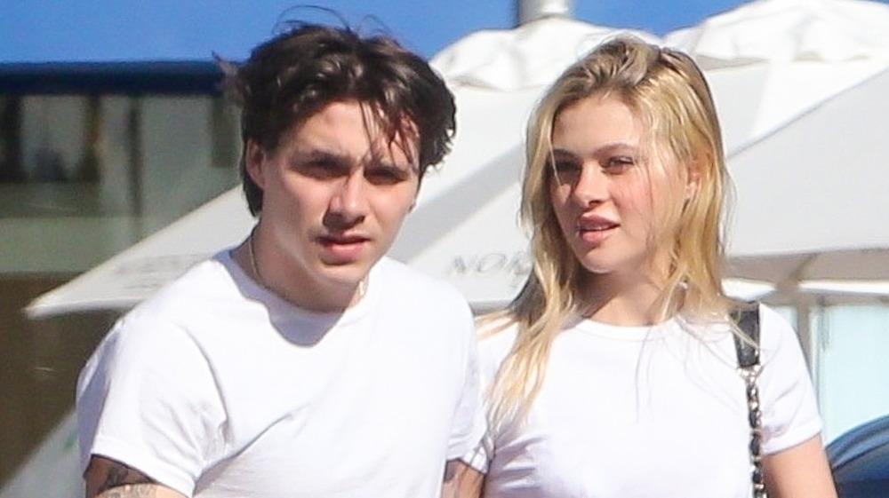 Brooklyn Beckham y Nicola Peltz vistiendo camisetas blancas a juego, caminando afuera