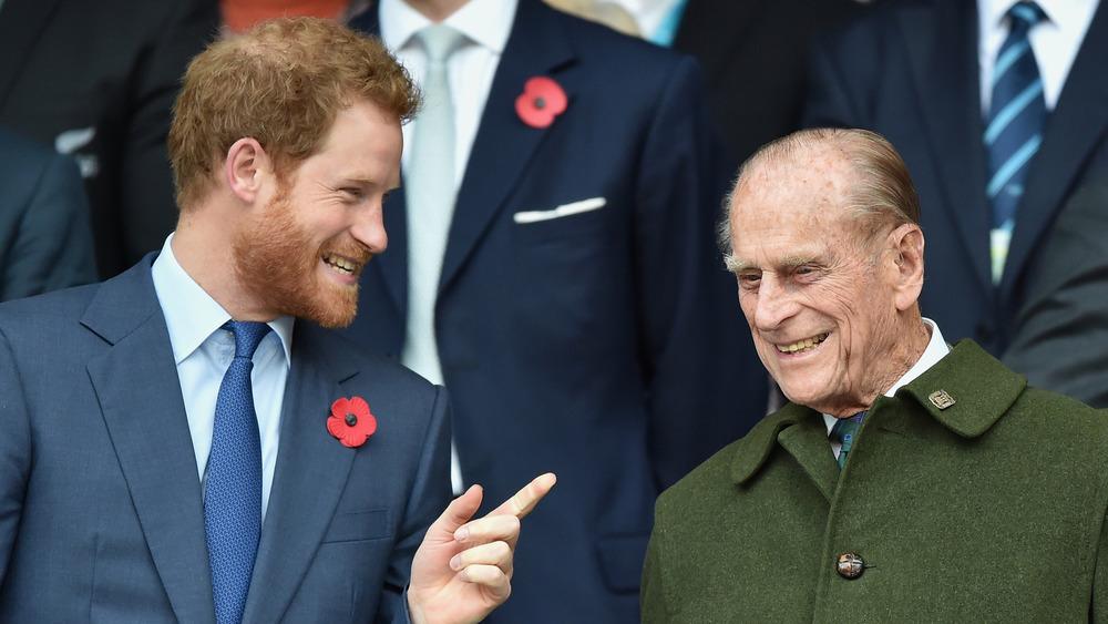 El príncipe Harry hablando con el príncipe Felipe
