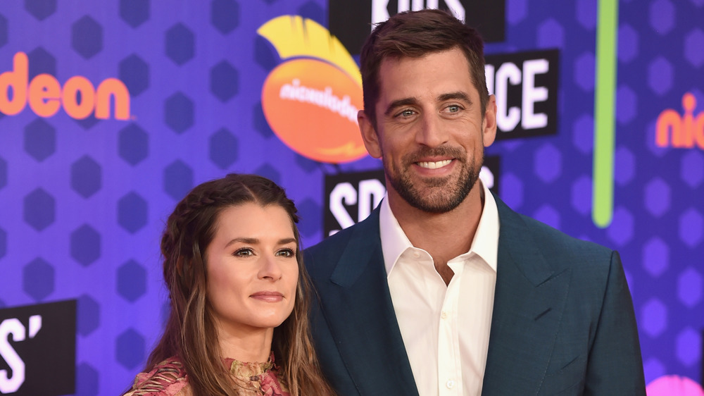 Danica Patrick y Aaron Rodgers sonriendo en el evento deportivo Nickelodeon Kids 'Choice