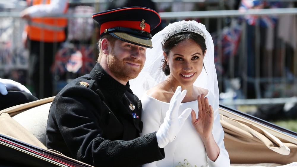 El príncipe Harry y Meghan Markle sonriendo y saludando a los fanáticos el día de su boda