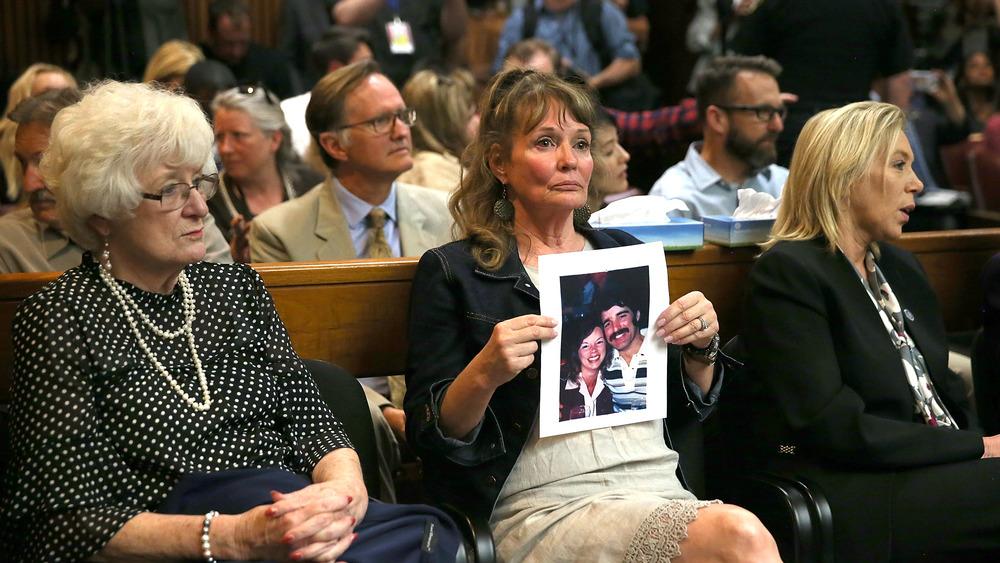 Un asistente sostiene una foto de las víctimas Cheri Domingo y su novio Gregory Sanchez