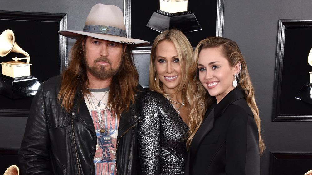 Miley Cyrus sonriendo con Billy Ray Cyrus y Tish Cyrus