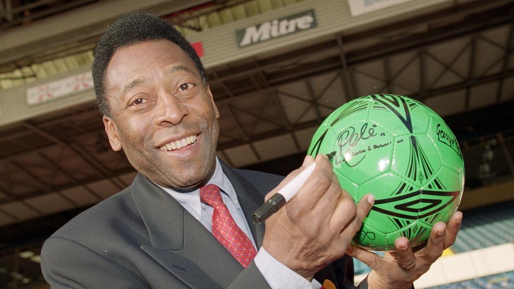 Pele firmando autógrafos en una pelota de fútbol