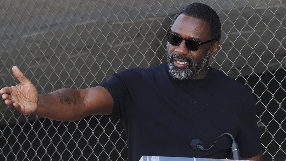 Idris Elba extendiendo su brazo