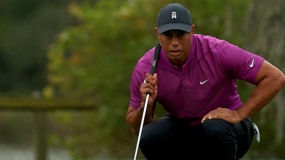 Tiger Woods se pone en cuclillas en el green