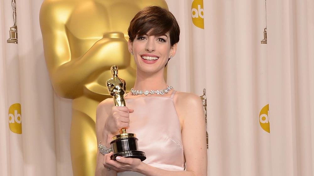 Anne Hathaway sosteniendo su premio Oscar en 2013