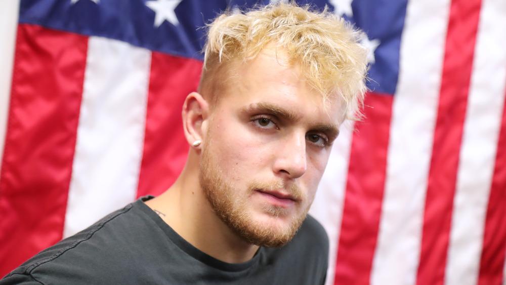 Jake Paul luciendo serio frente a una bandera estadounidense