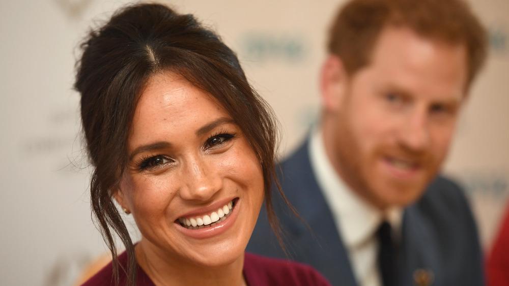 Meghan Markle sonriendo con el príncipe Harry de fondo