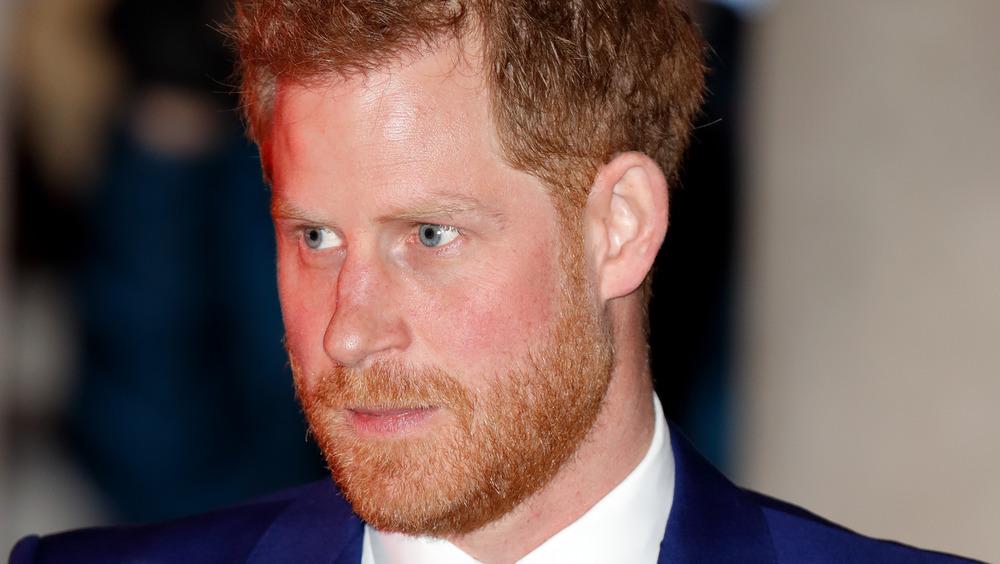 El príncipe Harry mirando a la distancia con un traje azul