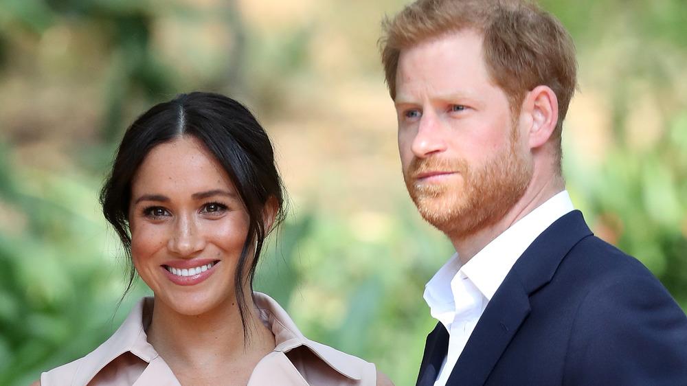 Meghan Markle y el príncipe Harry mirando hacia las cámaras