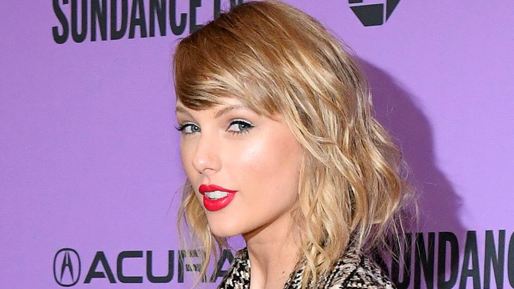 Taylor Swift sonriendo y mirando de reojo, con lápiz labial rojo brillante