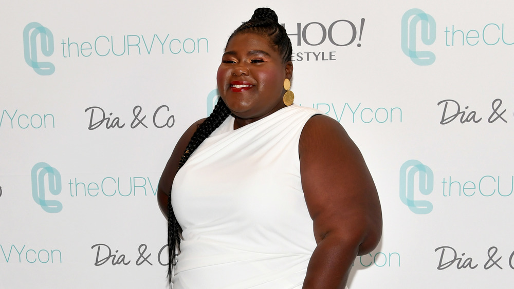 Gabourey Sidibe sonriendo con vestido blanco
