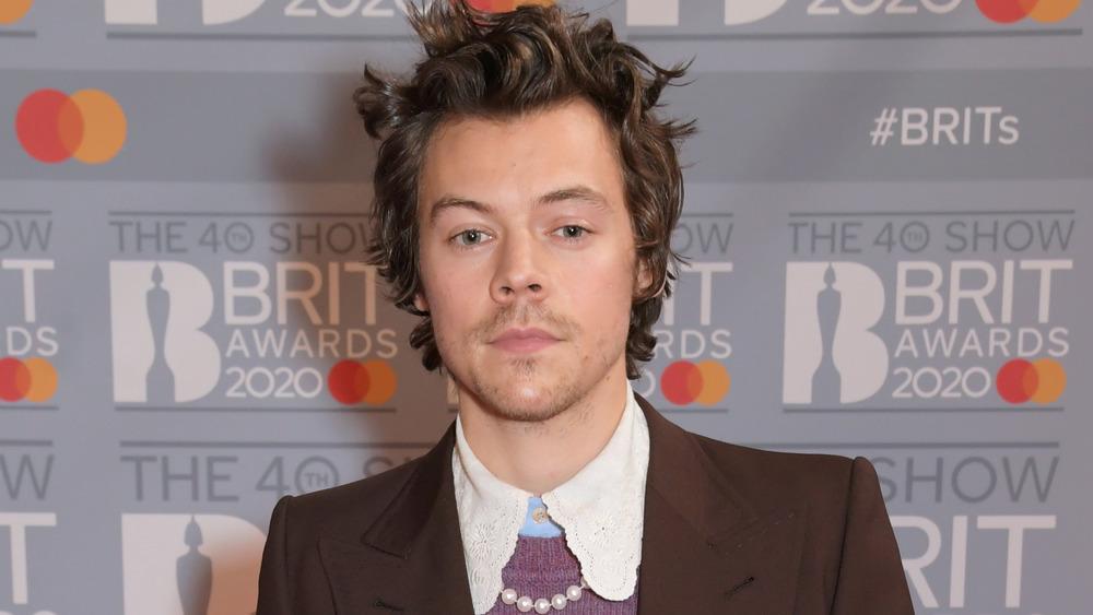 Harry Styles con una chaqueta marrón