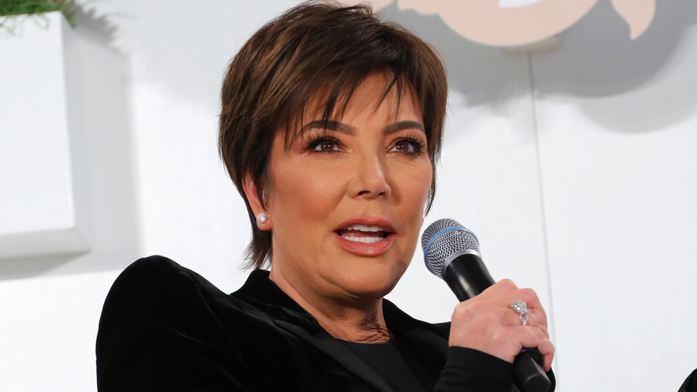 Kris Jenner sosteniendo un micrófono