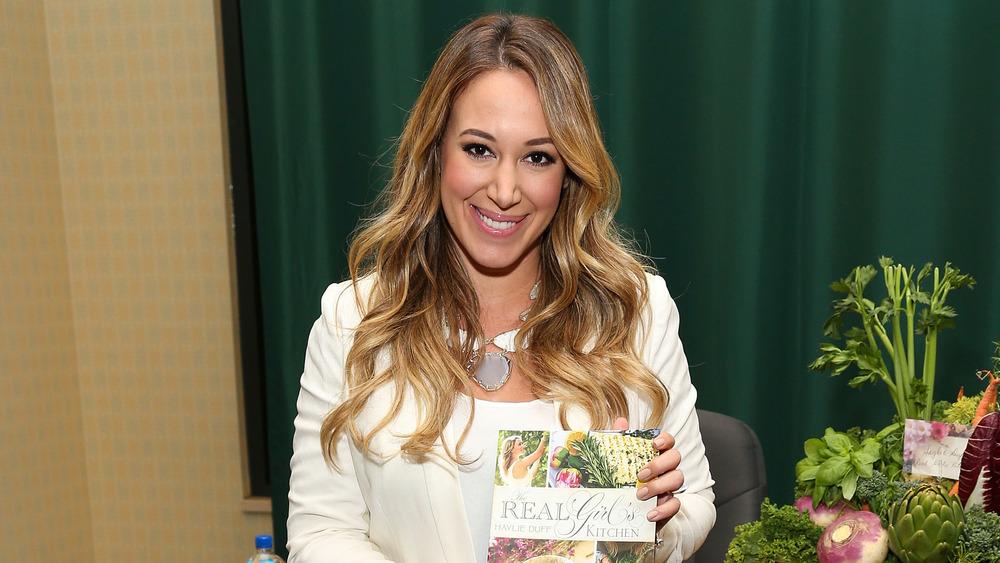 Haylie Duff sonriendo con su libro de cocina