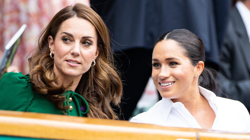 Kate Middleton y Meghan Markle se sientan y hablan juntas mirando a su derecha, mientras Markle sonríe