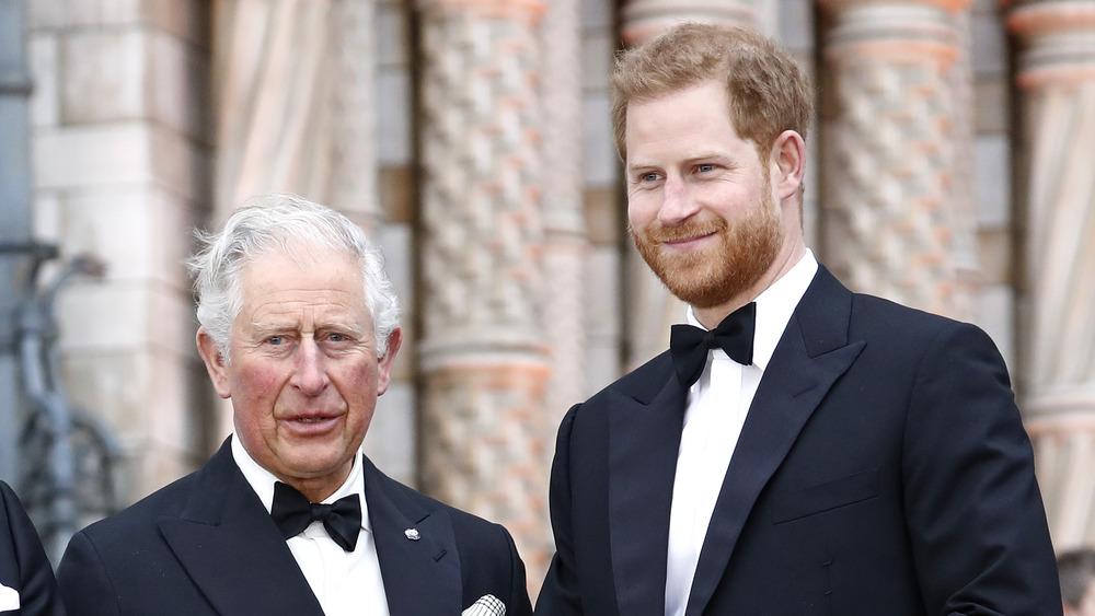 El príncipe Carlos y el príncipe Harry están uno al lado del otro en un evento