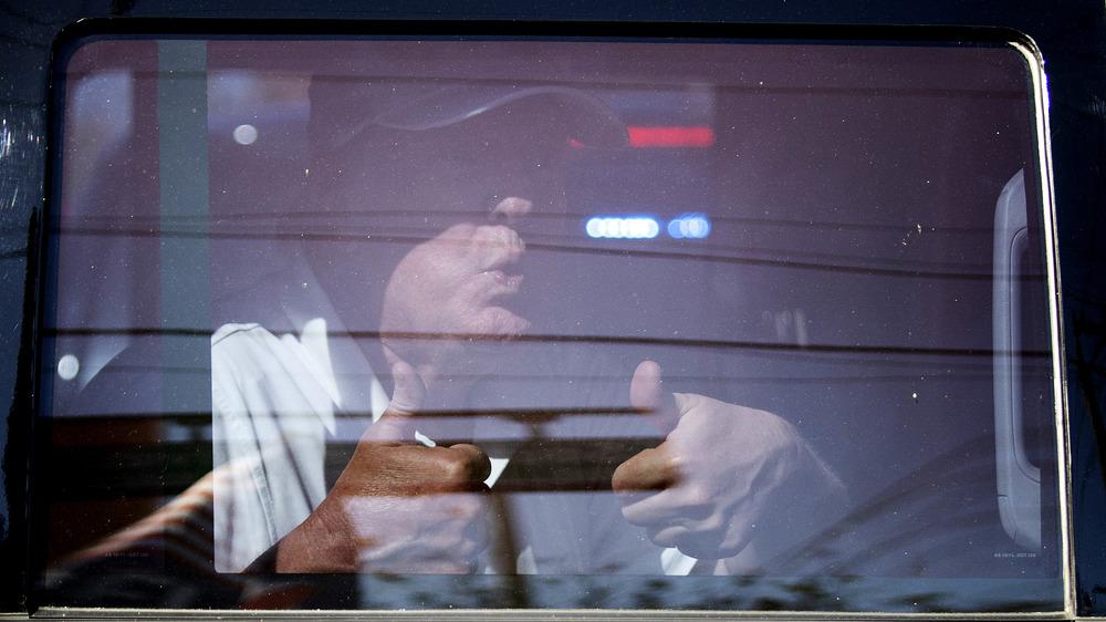 Donald Trump da a sus partidarios dos pulgares arriba desde el interior de un automóvil en Florida