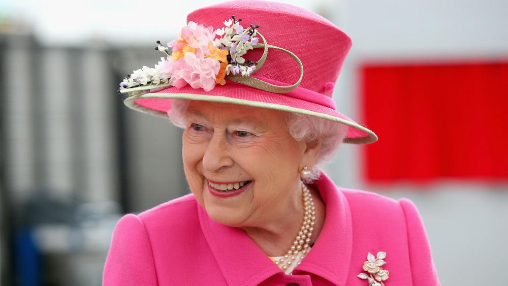 La reina Isabel II sonriendo en un evento vestida de rosa brillante