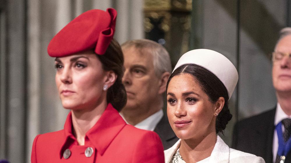 Una Kate Middleton con cara de piedra de pie frente a una sonriente Meghan Markle