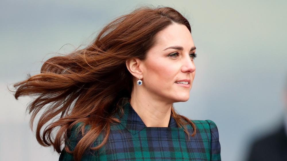 Kate Middleton sonriendo con el pelo al viento