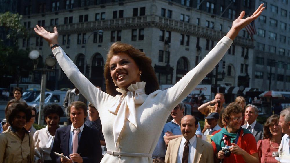 Vanessa Williams levantando los brazos en el aire frente a una multitud