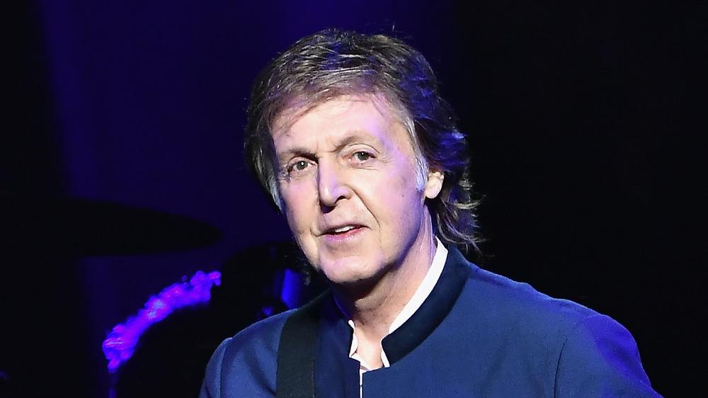 Paul McCartney con una guitarra en el escenario.