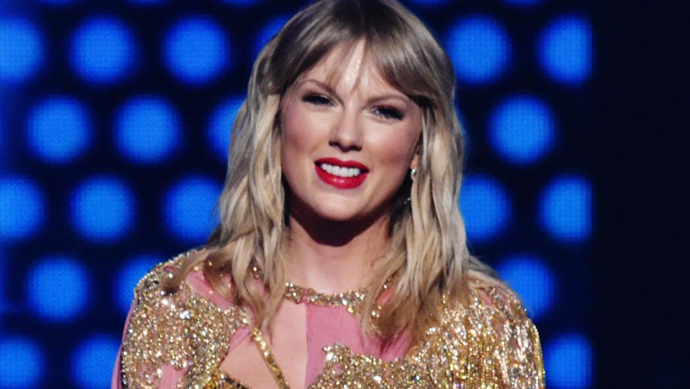 Taylor Swift sonriendo con gorro de Papá Noel, gargantilla y lápiz labial rojo