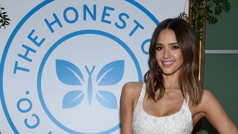 Jessica Alba delante del logo de The Honest Company.