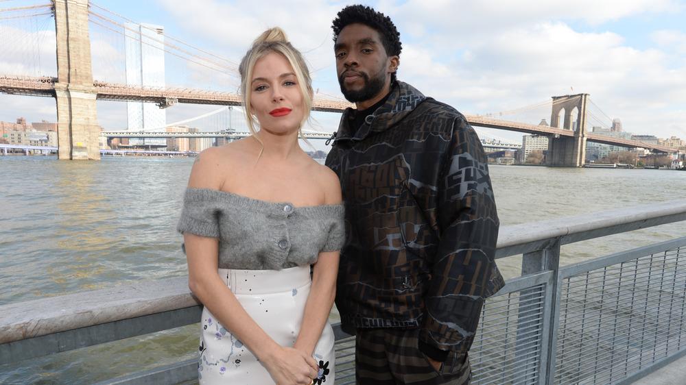 Sienna Miller y Chadwick Boseman delante del puente