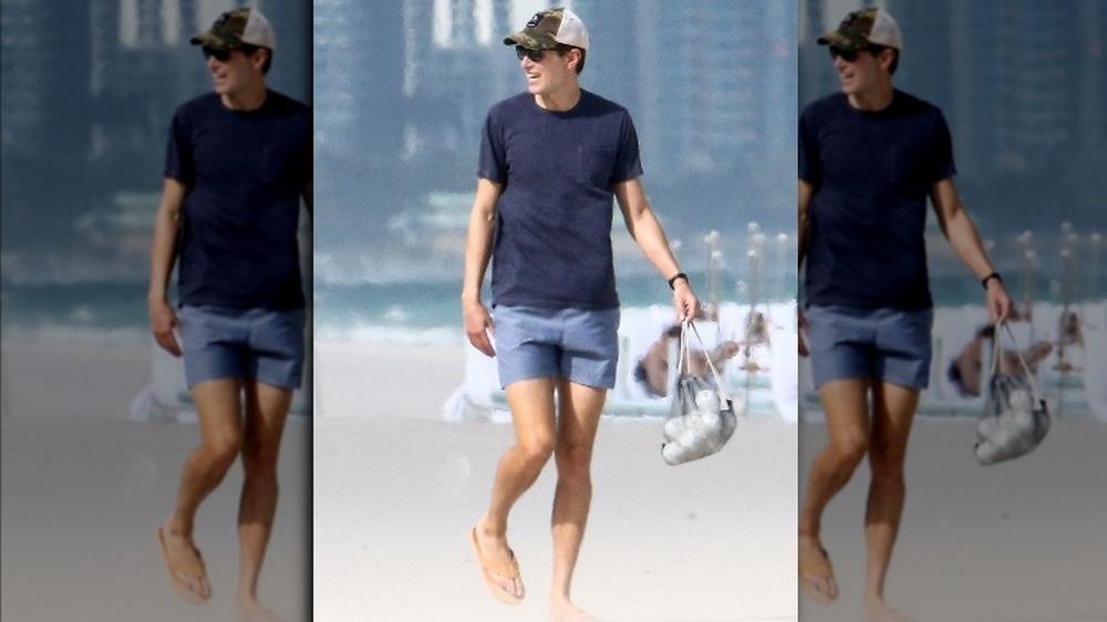 Jared Kushner en la playa sonriendo, en traje de baño y sandalias