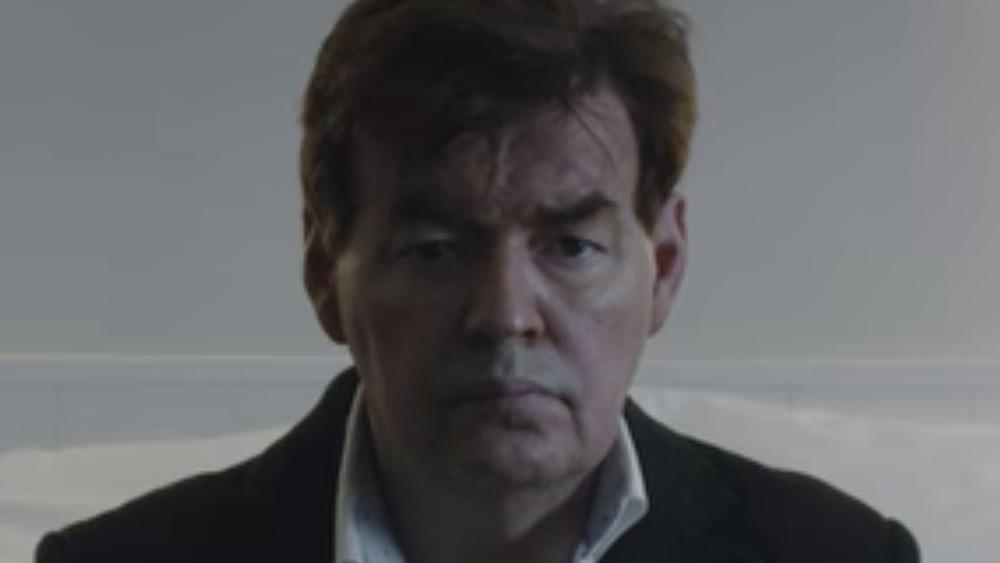 Bernard Wesphael se ve serio mientras está sentado en una cama
