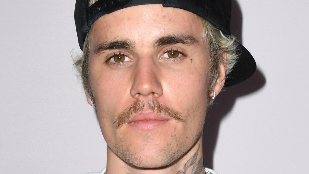 Justin Bieber luciendo un bigote, un sombrero al revés y una mirada seria