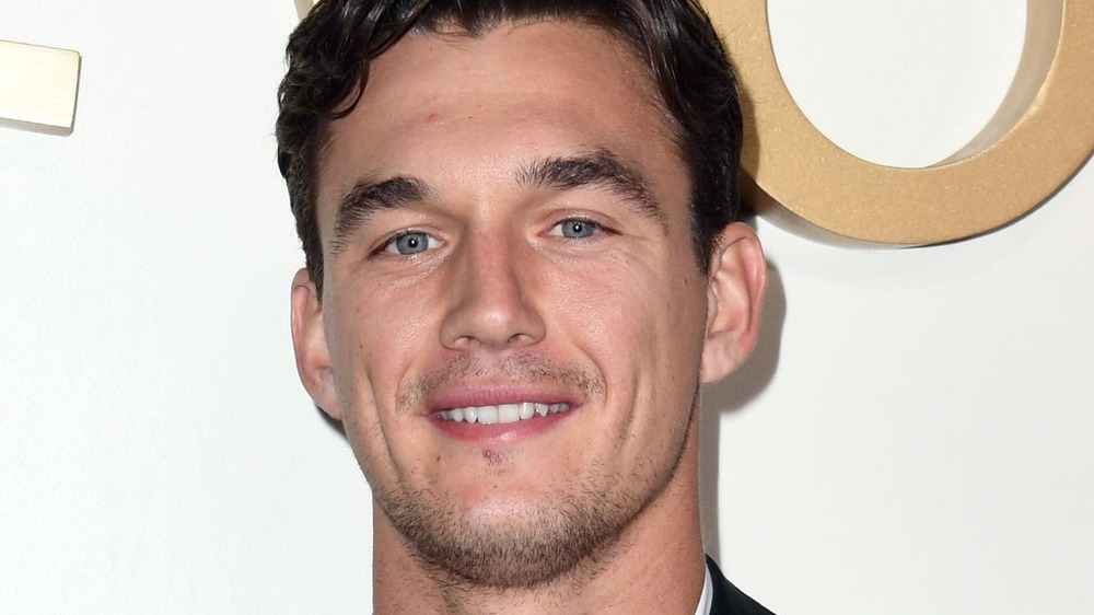 Tyler Cameron sonriendo en la alfombra roja
