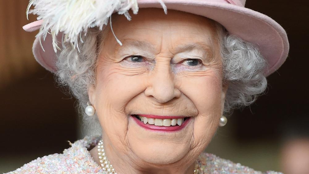 La reina Isabel II sonriendo en un evento vestida de rosa claro