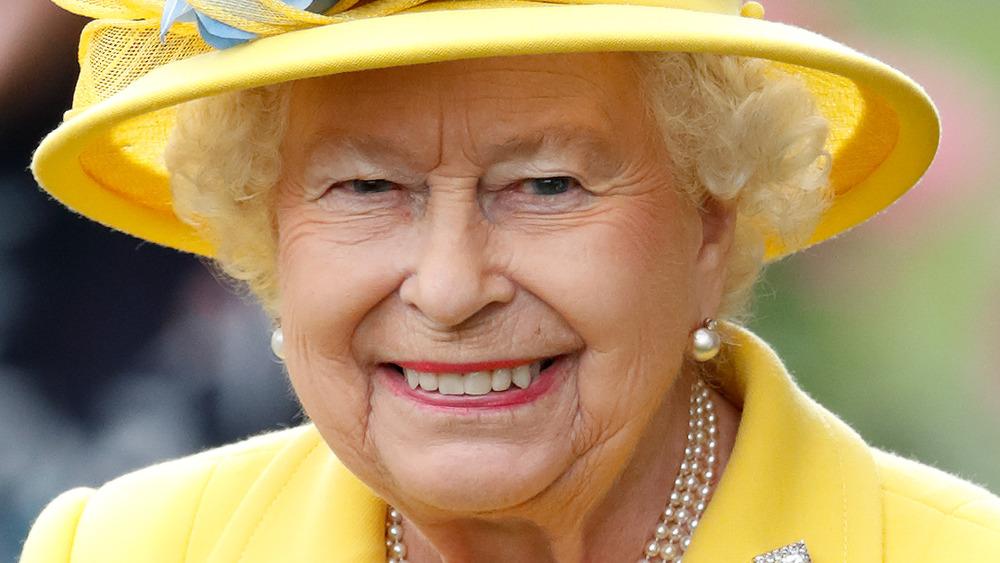 La reina Isabel II sonriendo con un traje amarillo y un sombrero a juego