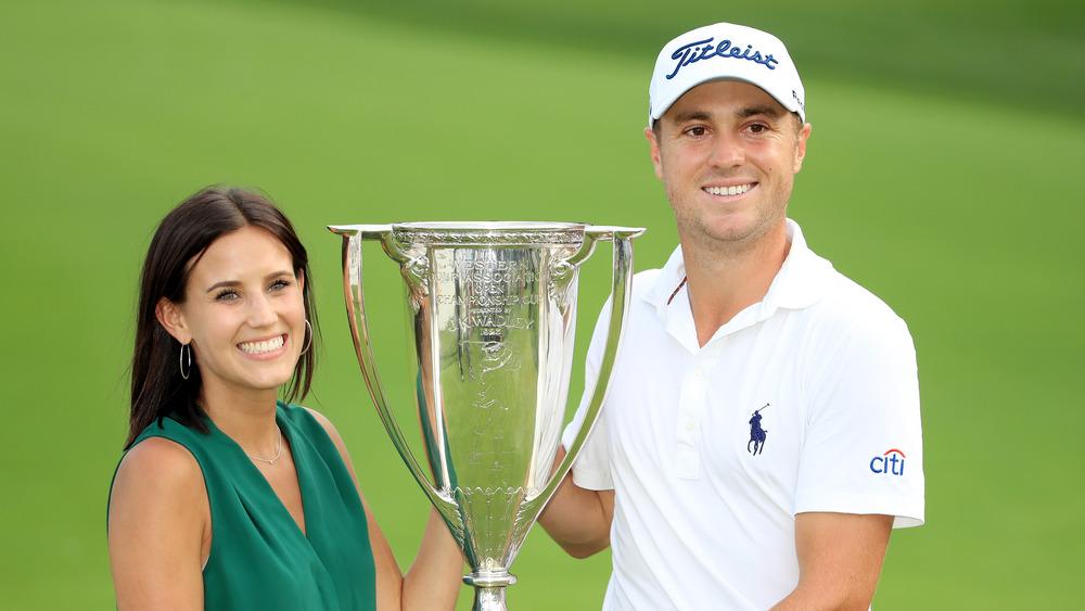 Jillian Wisniewski y Justin Thomas sostienen una copa de golf