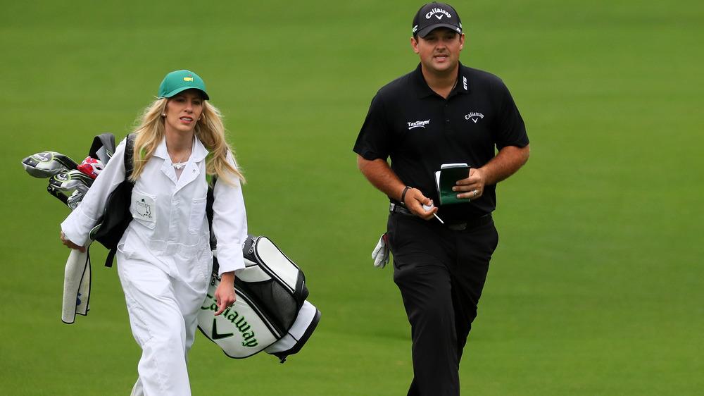 Justine Reed, trabajando como caddie, vestida de blanco, vestida con un odio, sosteniendo palos de golf;  Patrick Reed, vestido todo de negro y sombrero, en el campo de golf